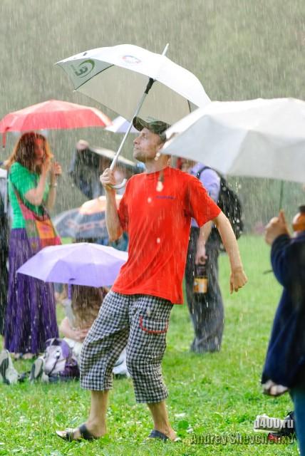 танцует под дождем с зонтом